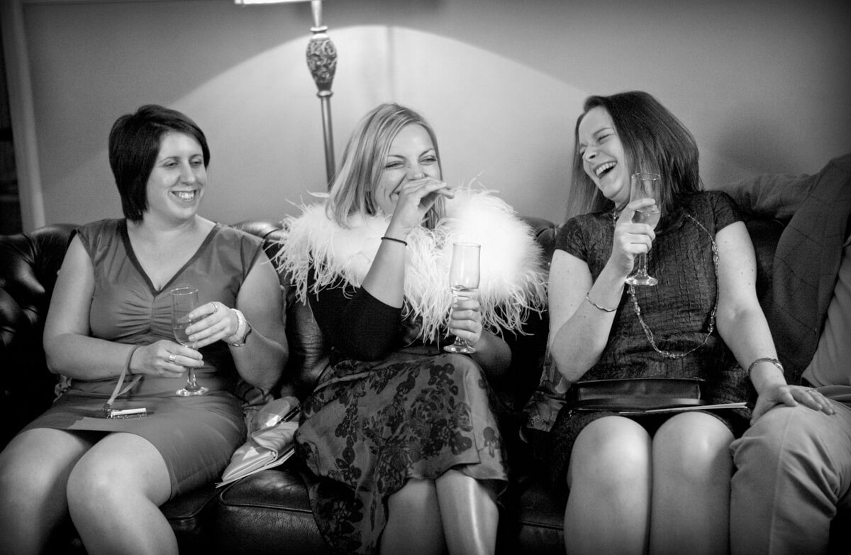 Ladies at wedding laughing on sofa at Lemore Manor Herefordshire