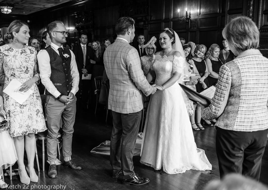Bride and groom taking wedding vows with guests looking on