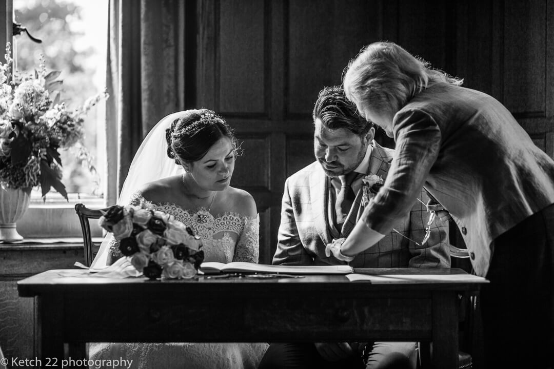 Bride and groom signing registrar at Whitney Court