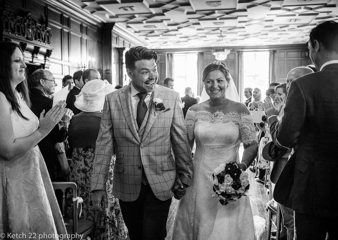 Bride and groom leaving ceremony room with wedding guests cheering