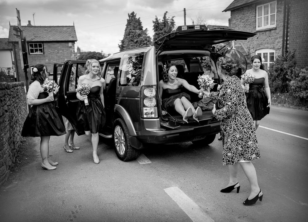 Bridesmaids getting out of car at wedding