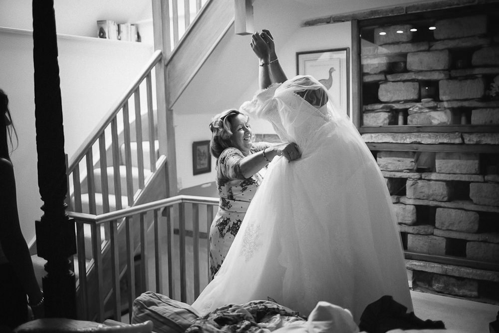 Mother helping bride put her wedding dress on at Upper Court,Gloucestershire