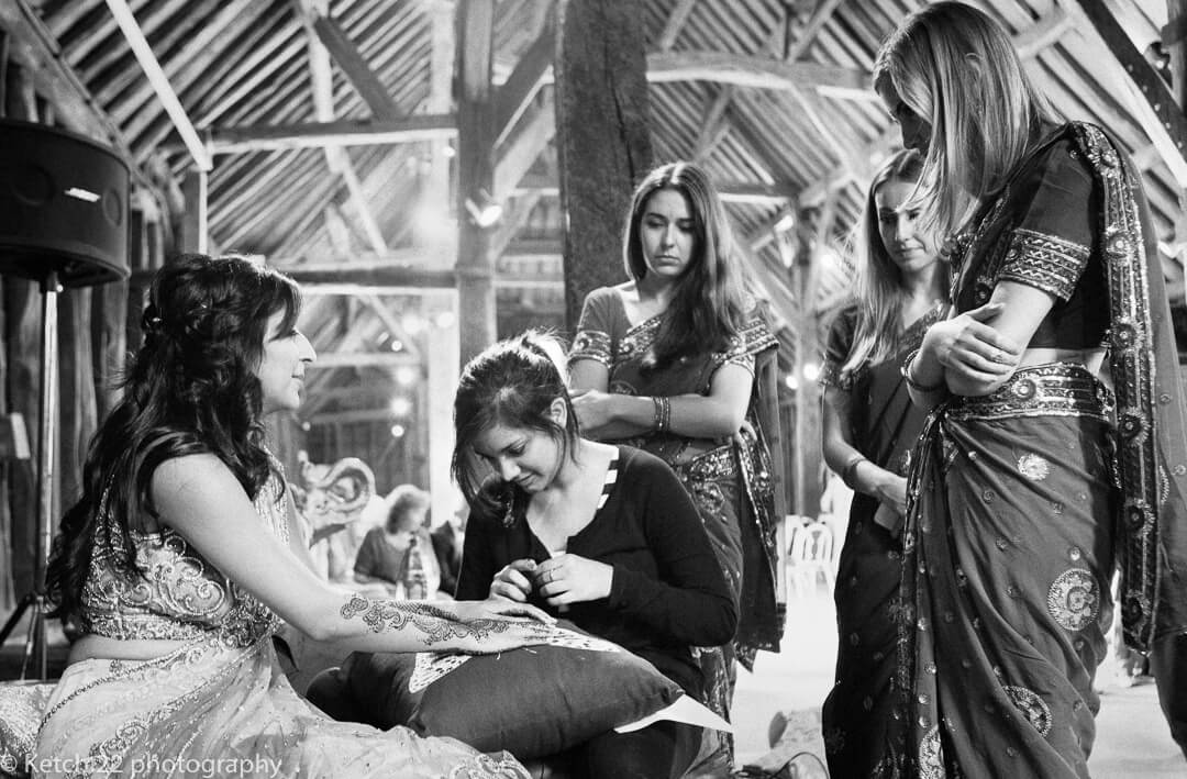 Hindu bride chatting to friends on Indian Henna evening in London