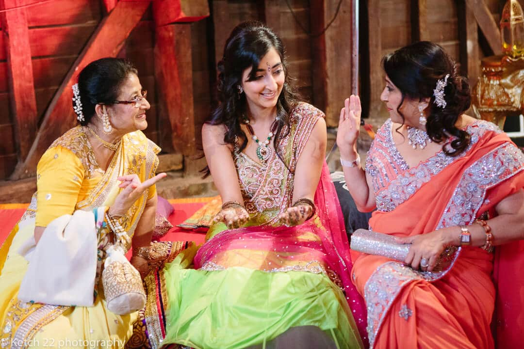 Bride shows friends her painted hands at mehendi and sangeet night