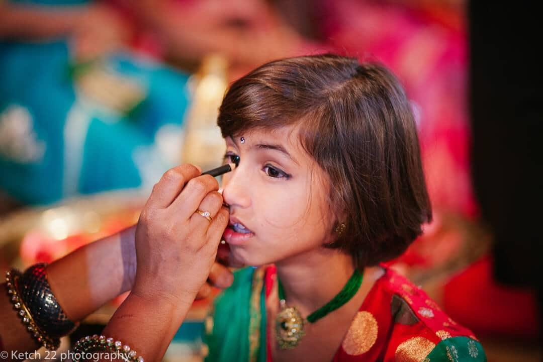 Little girl having make up applied at Indian wedding