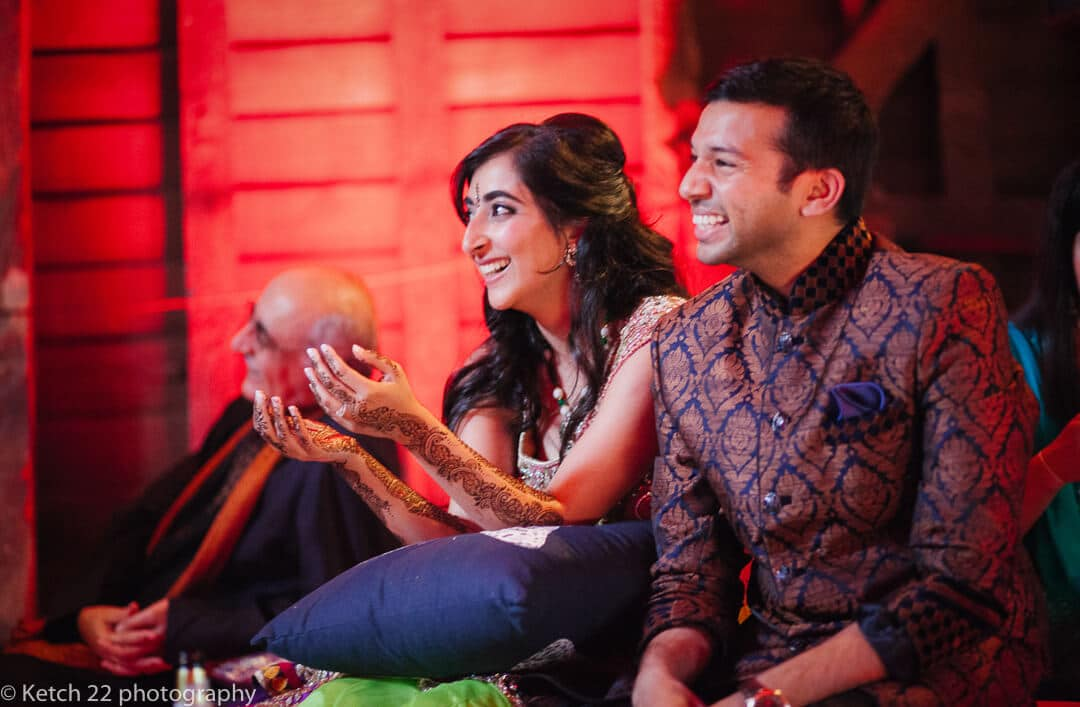 Bride and groom in traditional costume laughing at indian wedding night