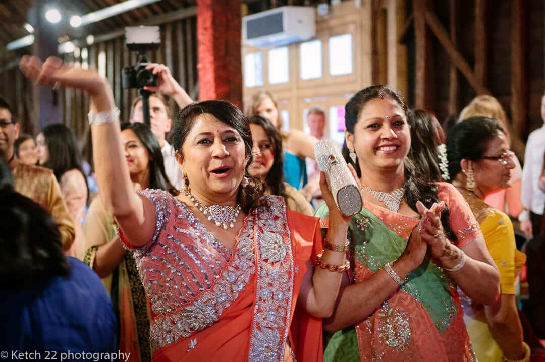 Mothers in traditional hindu costume cheering at indian henna night