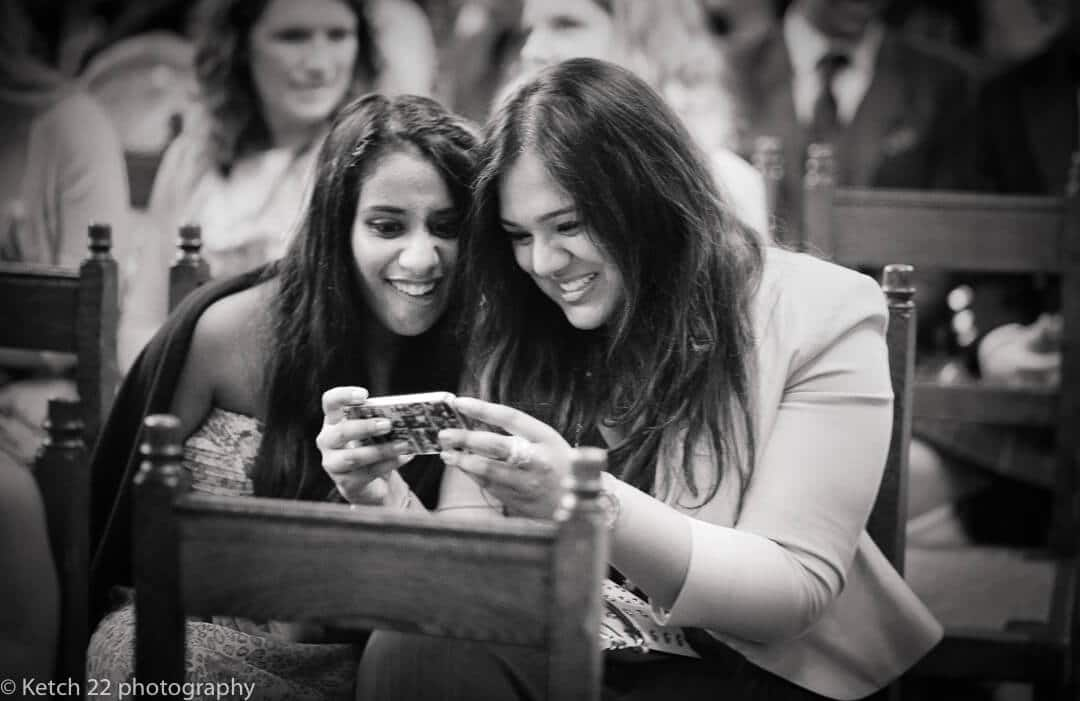 Wedding guests looking at phone at Civil wedding ceremony in London