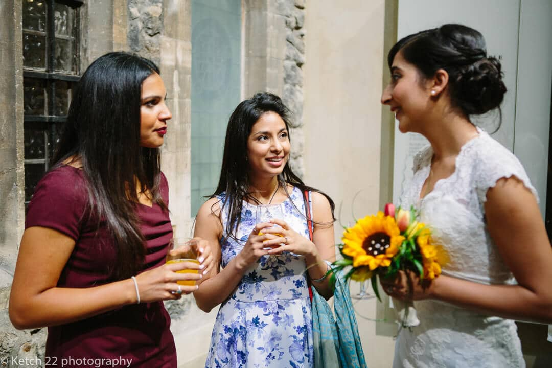 Bride with yellow sunflowers talking to her friends at wedding reception