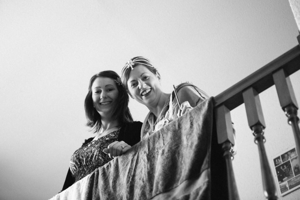 Bride and bridesmaid leaning on banister and smiling at wedding in Shropshire