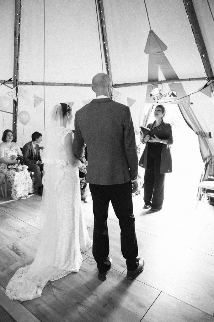 Bride and groom at wedding ceremony in vintage tent in Shropshire