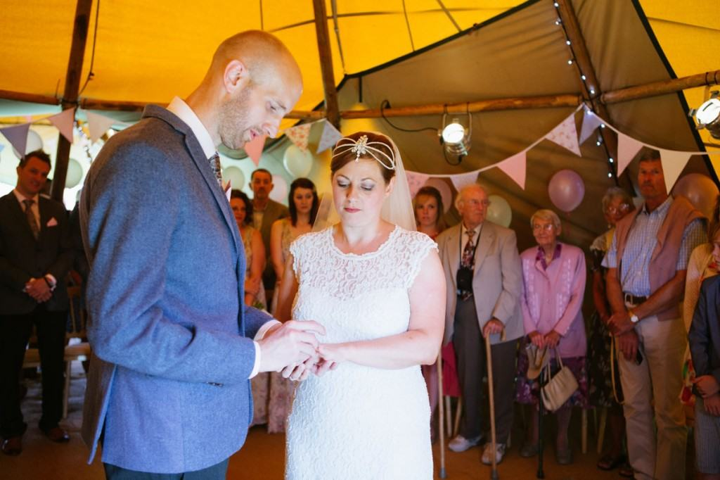 Bride and groom exchange rings at wedding ceremony in vintage marquee in Shropshire