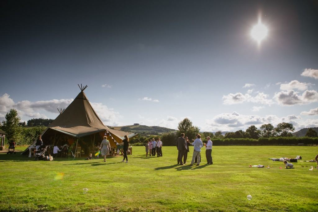 Wedding guests outside vintage marquee in Shropshire countryside