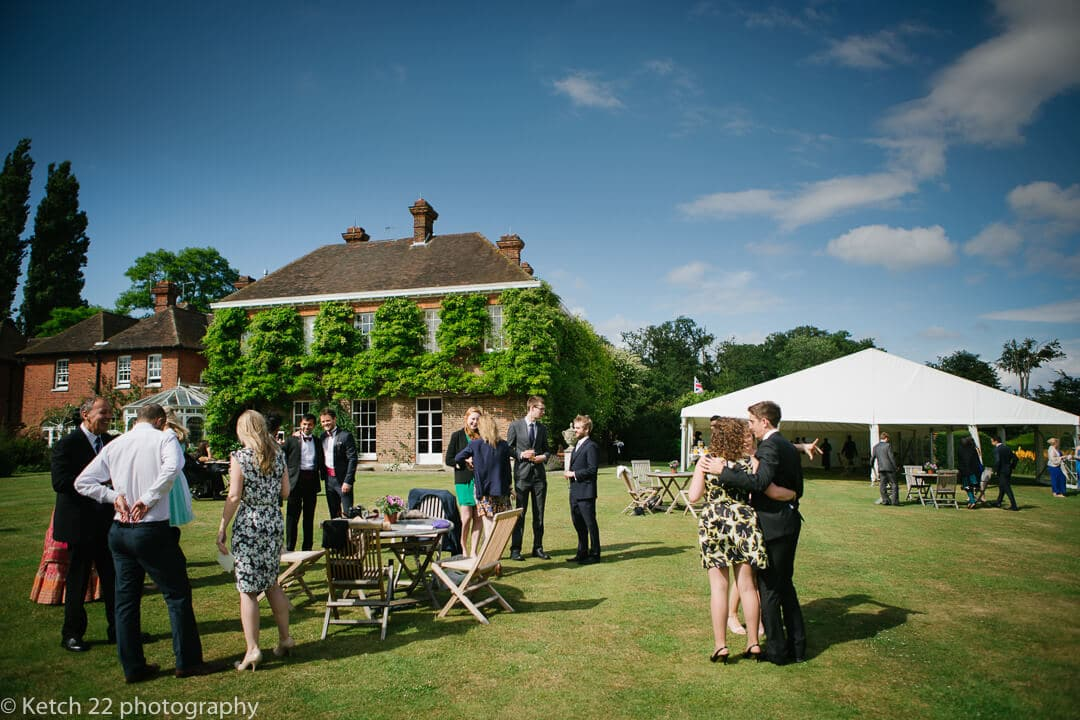 Wedding guests having canapes and drinks on lawn at Micklefield Hall