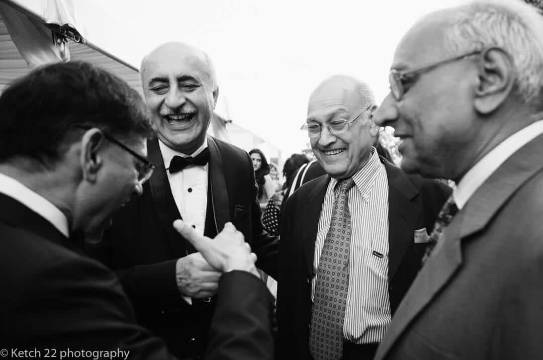 Father of bride and uncles laughing at Hindu wedding