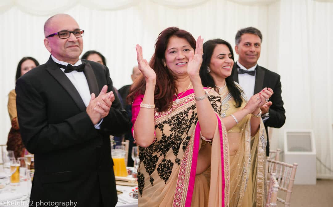 Hindu wedding guests clapping