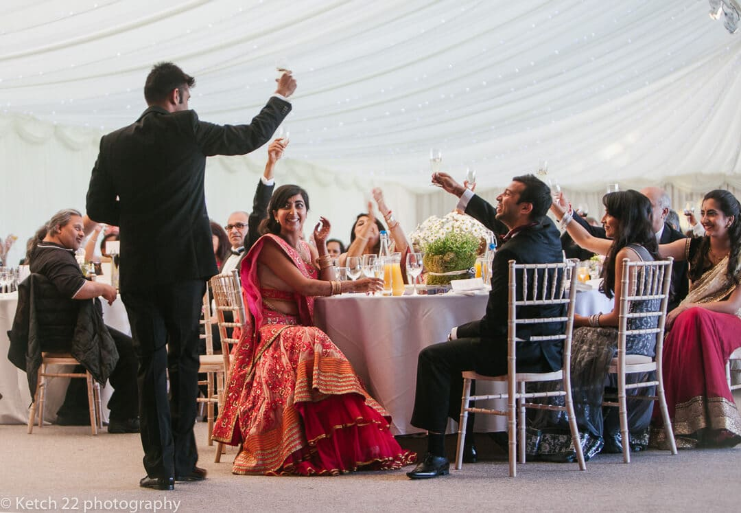 Best man and wedding guests toasting at Hindu wedding speeches