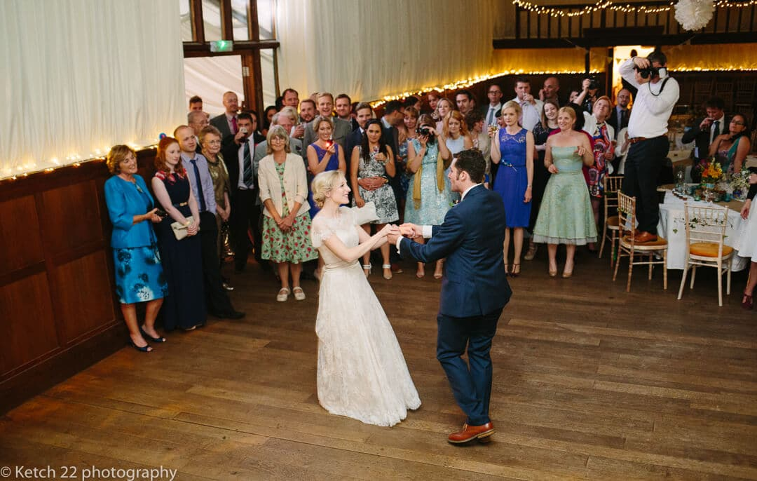 Bride and groom enjoy first dance with guests watching at How Caple Court