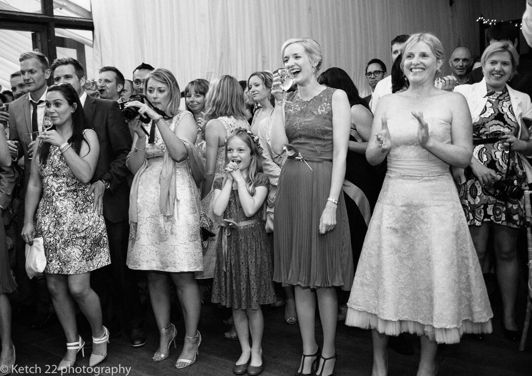 Documentary wedding photo of guests watching bride and groom dance