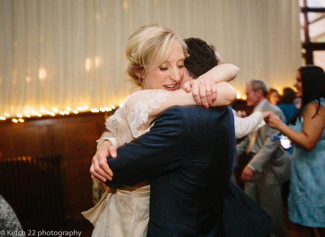 Bride hugging groom at first dance