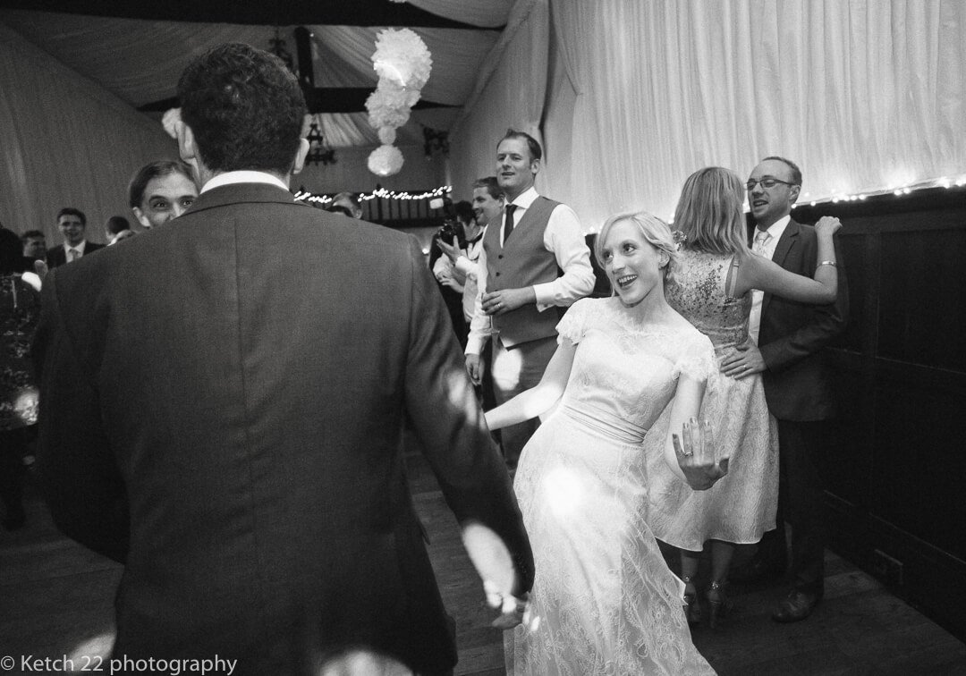 Candid photo of bride and groom dancing at wedding reception
