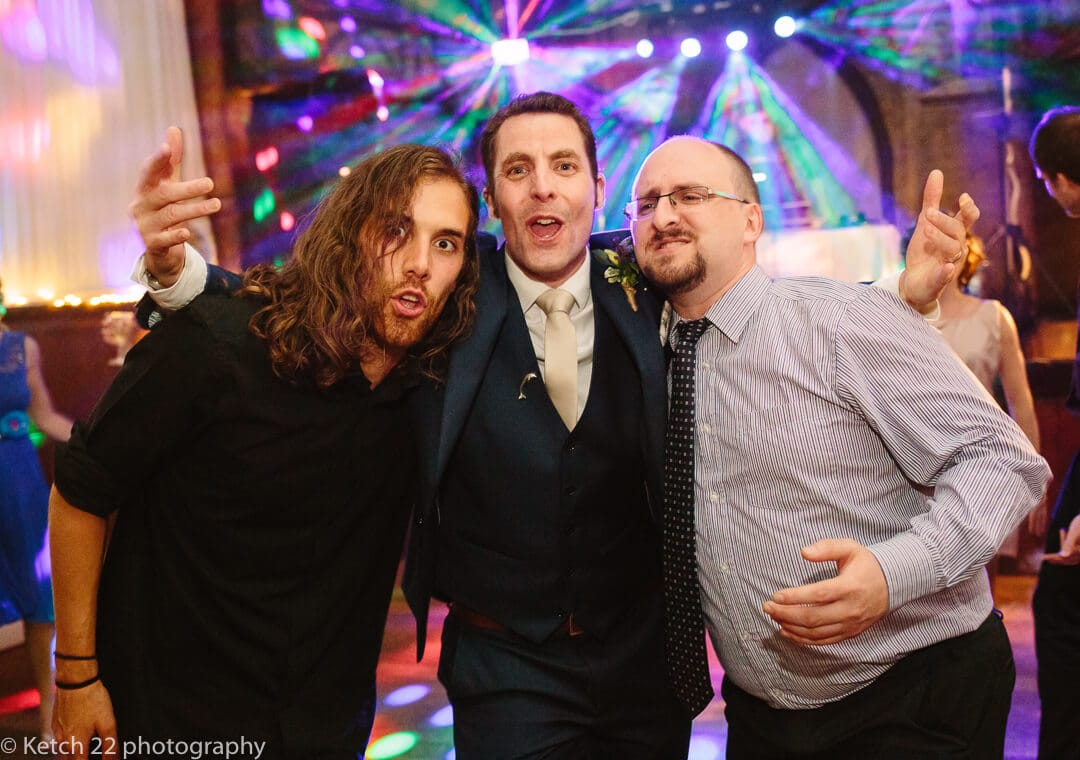 Funny portrait of groom and his friends at wedding reception