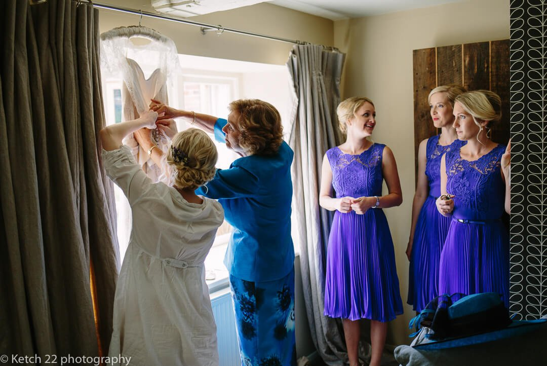 Story telling photo of bride and mother getting wedding dress ready