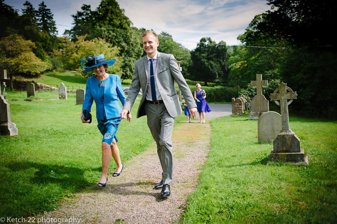 Mother of bride and friend arriving at church for rural wedding