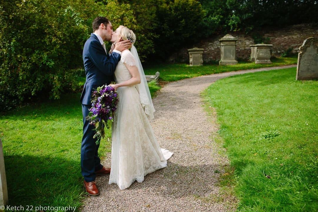 Romantic portrait of bride and groom kissing in Church yard