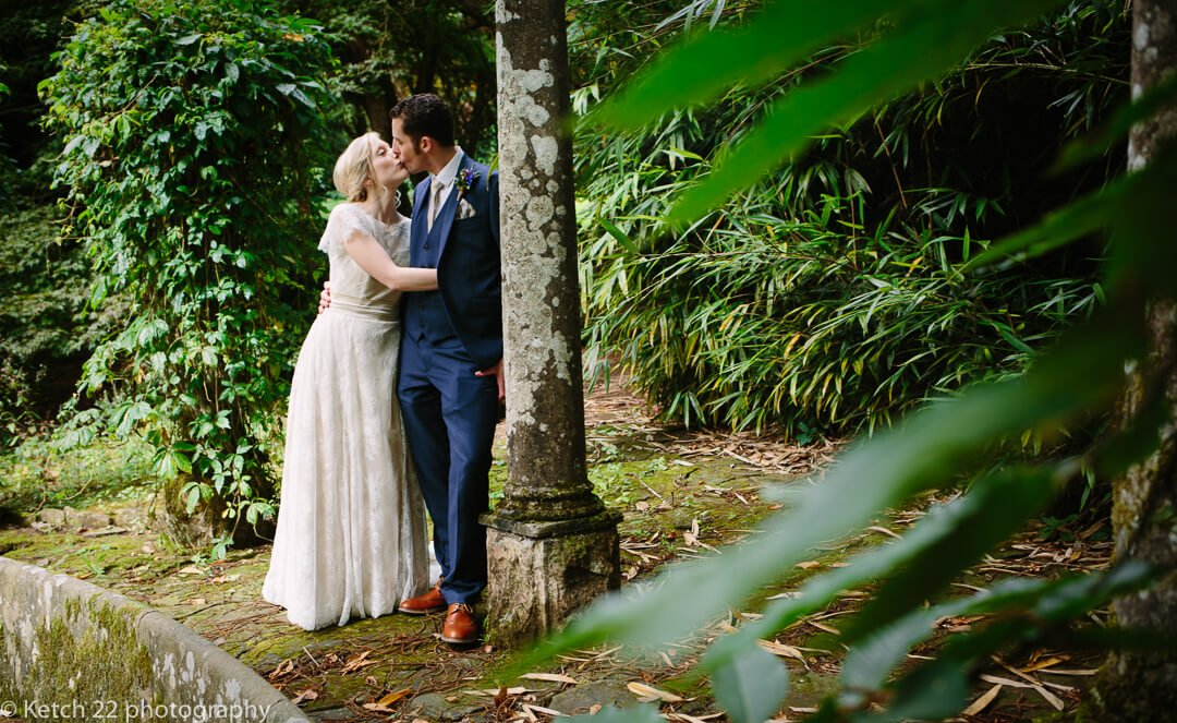 Bride and groom kissing in garden at How Caple Court wedding