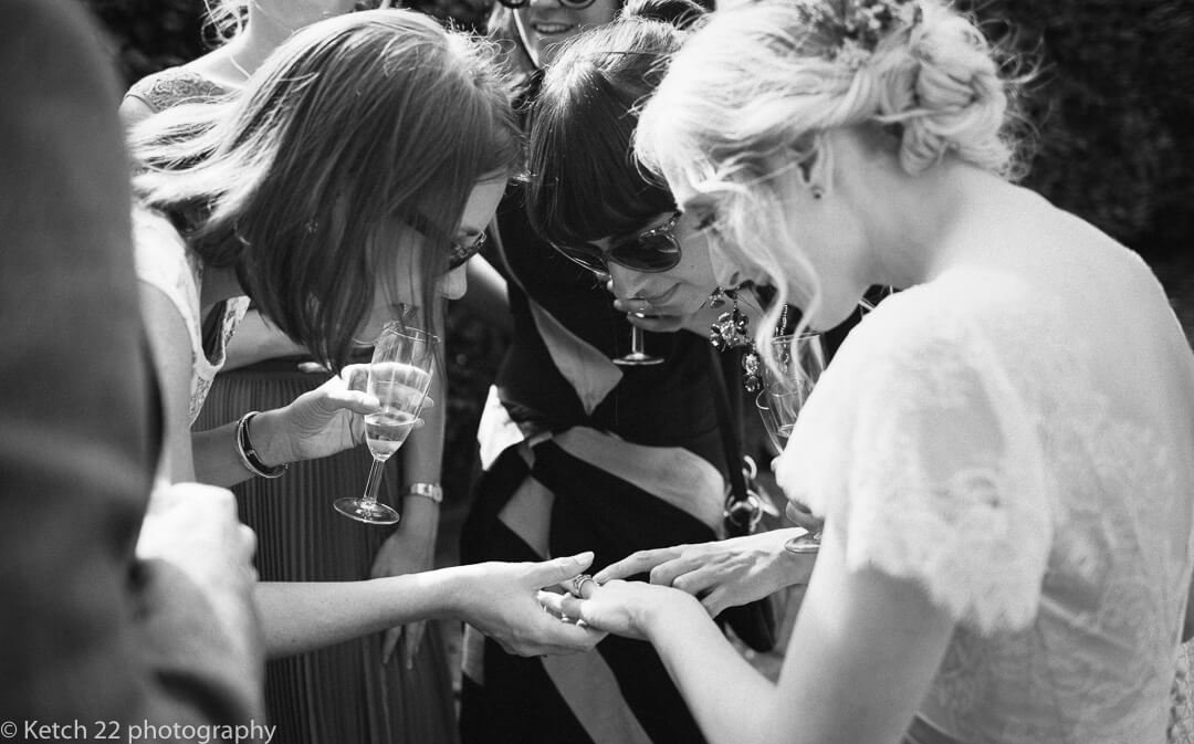 Bride showing off her wedding ring to friends