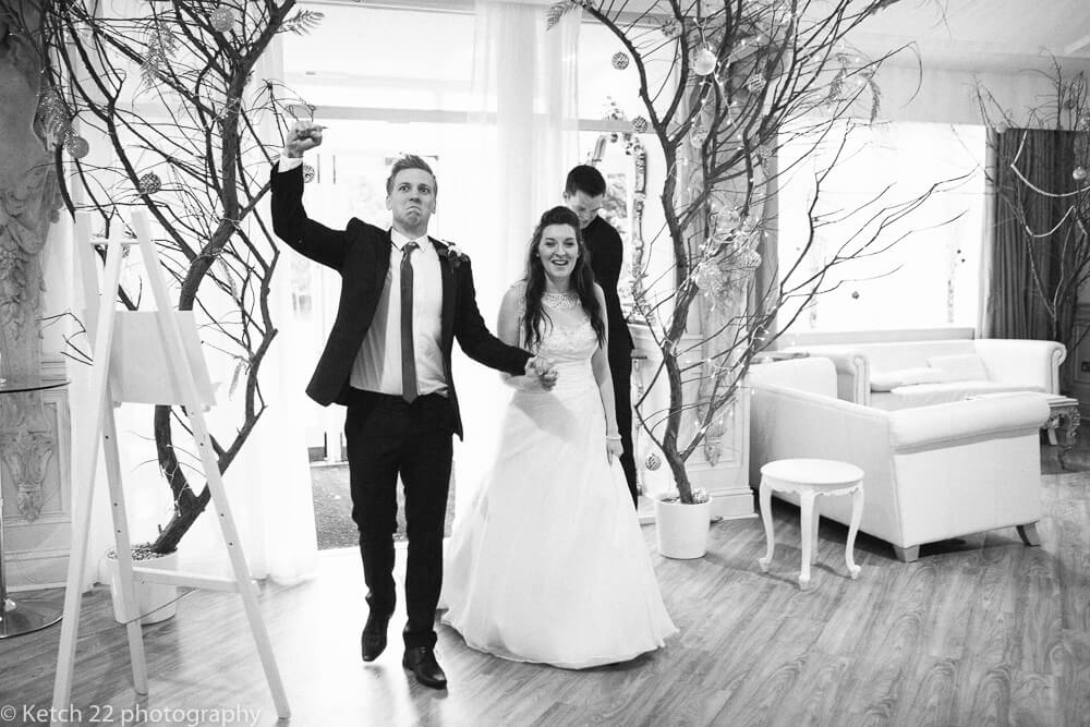 Bride and groom entering dining room at Manor by the lake wedding Gloucestershire