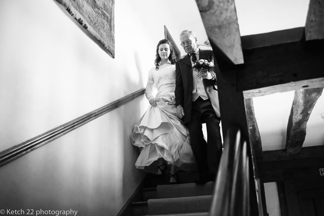 Father and bride descending stairs at Country house wedding