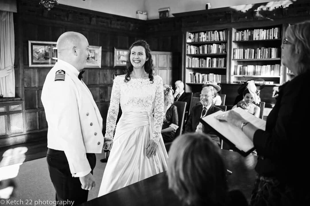 Bride and groom exchanging vows in Library at Brinsop Court