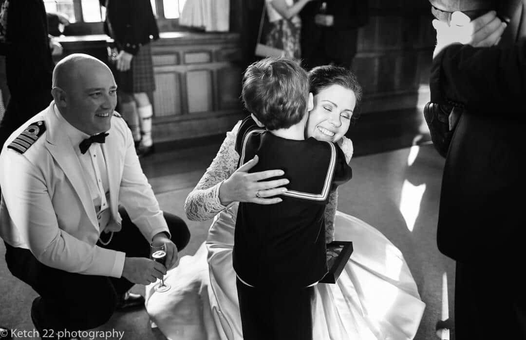 Bride hugging small boy at small wedding