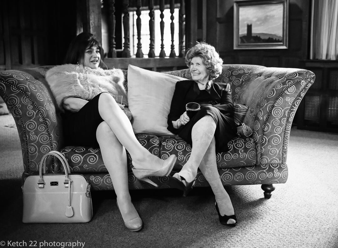 Wedding guests relaxing on sofa and chatting