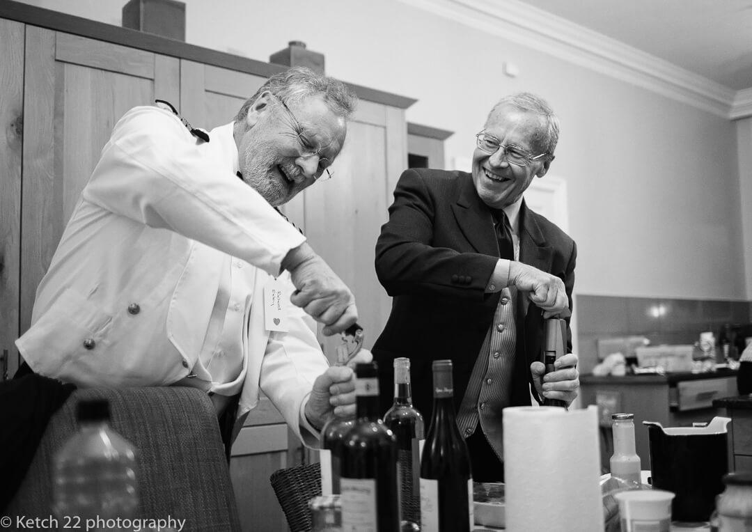 Wedding guests opening wine bottles