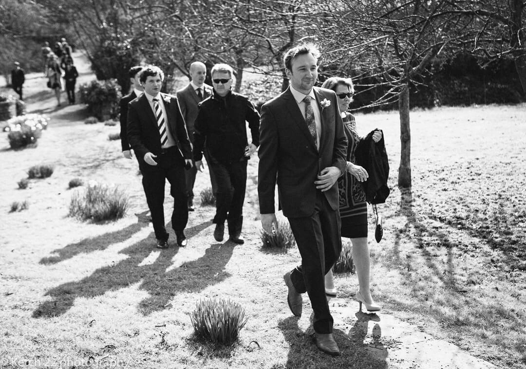 Groom and wedding guests walking to church in Herefordshire