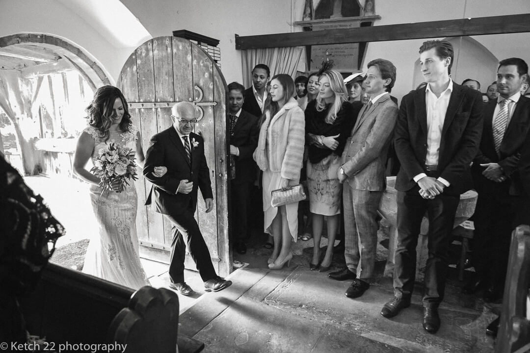 Father and bride enter church with wedding guests looking on in Herefordshire