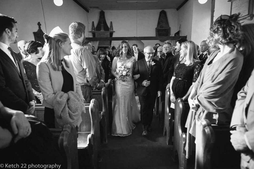 Reportage wedding photo of father and bride walking down church aisle