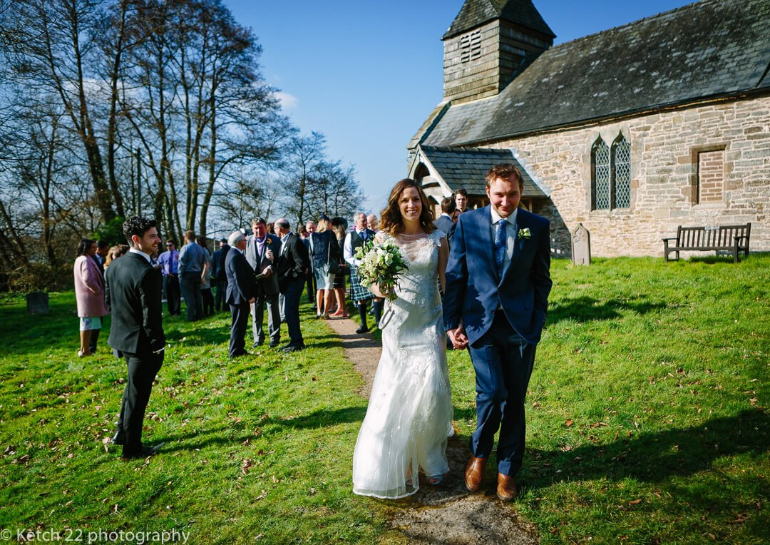 Bride and groom walking from church after wedding ceremony at Dewsall Court