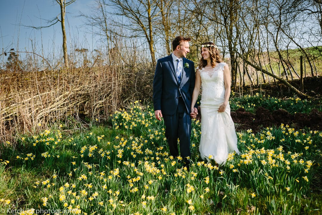 Bride and groom walking amongst daffodils at spring wedding at Dewsall Court