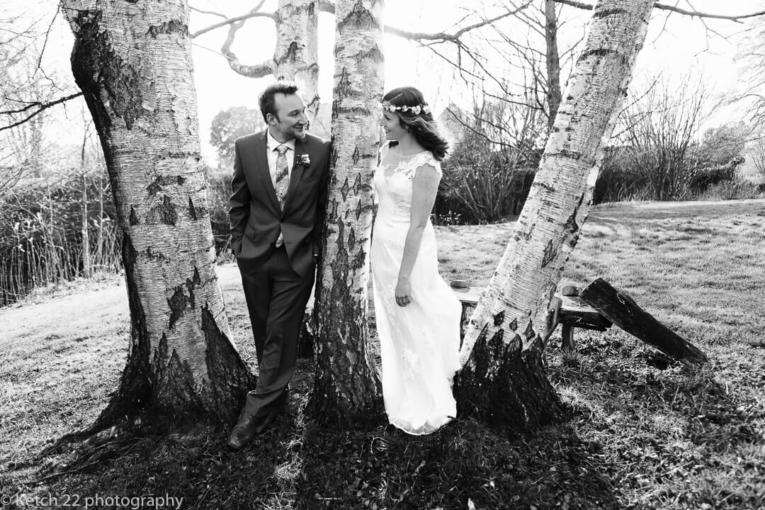 Bride and groom leaning on birch tree at Spring wedding in Herefordshire