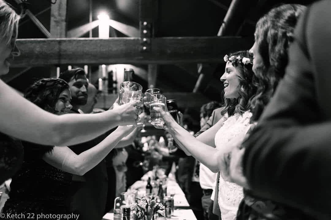 Bride toasting after speeches at barn wedding