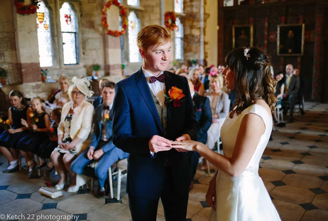 Groom putting wedding ring on brides finger at Castle wedding