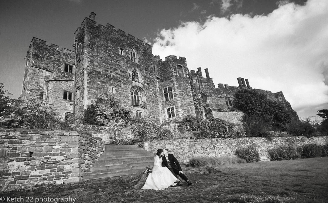 Bride and groom kissing in front of Berkeley castle in Gloucestershire