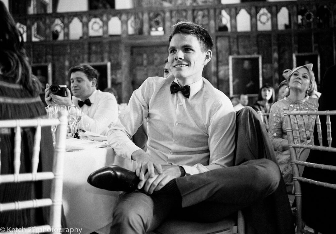 relaxed wedding guest listening to wedding speeches