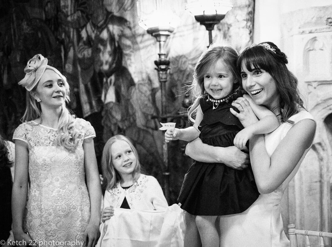 Bride holding laughing flower girl at Winter wedding