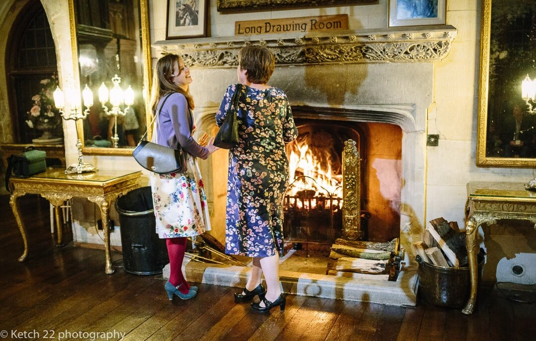 Guests warming themselves by warming fire at Winter wedding at Berkeley Castle