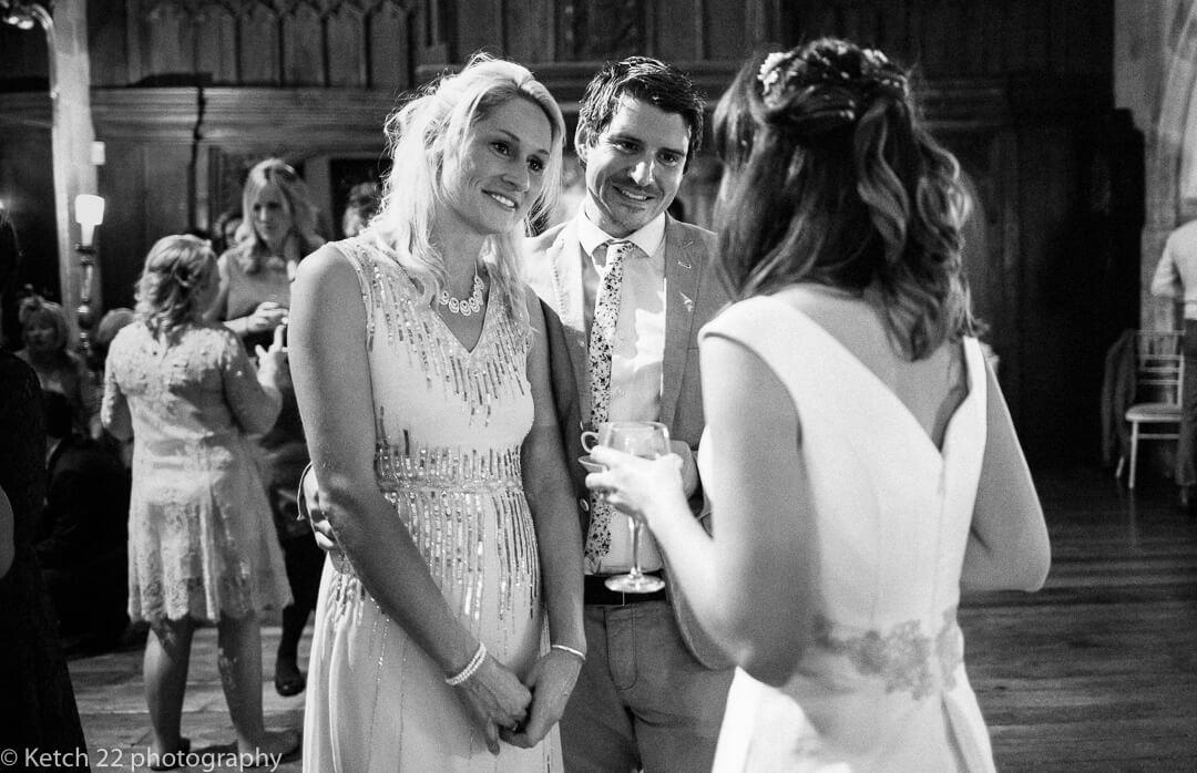 Wedding guests cahting to bride at reception
